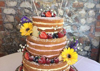 naked wedding cake fresh fruit fresh flowers sunflowers