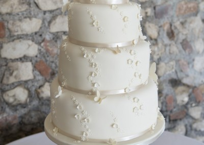 4 tier ivory wedding cake decorated with small blossom flowers and butterflies
