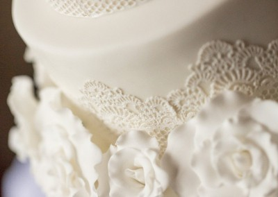 All white wedding cake with white edible lace and white sugar roses