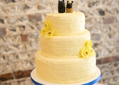 Rustic buttercream wedding cake decorated with yellow gerbera flowers and fondant pug toppers