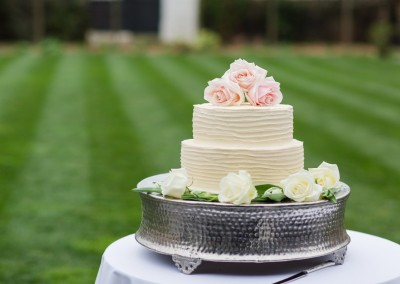 Two tier buttercream wedding cake decorated with fresh roses