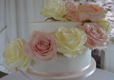 Two tier wedding cake decorated with fresh cascading pink and ivory roses